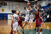Kingswood's Russell Lucia goes up for a shot against Belmont's Caleb Burke during the boys finals Friday evening for the annual holiday basketball tournament.  (Karen Bobotas/for the Laconia Daily Sun)