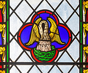 Close up of 19th century stained glass window in church of Saint Andrew, Wissett, Suffolk, England, UK - Pelican feeding young