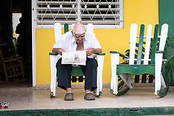 14 September 2015, Viñales, Cuba: An old man reads the newspaper on his front porch, in the UNESCO world heritage site of Vinales / Viñales, Cuba.
