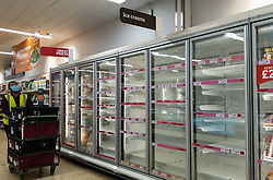 © Licensed to London News Pictures. 04/06/2021. London, UK. A member of staff walks past empty shelves in a Sainsbury's supermarket in north London store, as it runs out of ice cream during the heatwave. Photo credit: Dinendra Haria/LNP