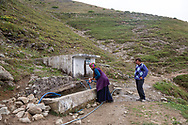 Yilmaz Civelek, right, and his wife Esma, left, collecting water from a natural spring in their small village of Alaca Yaylası, in Turkey's northern Pontic mountains, and a common place for whistling as a method of communication.