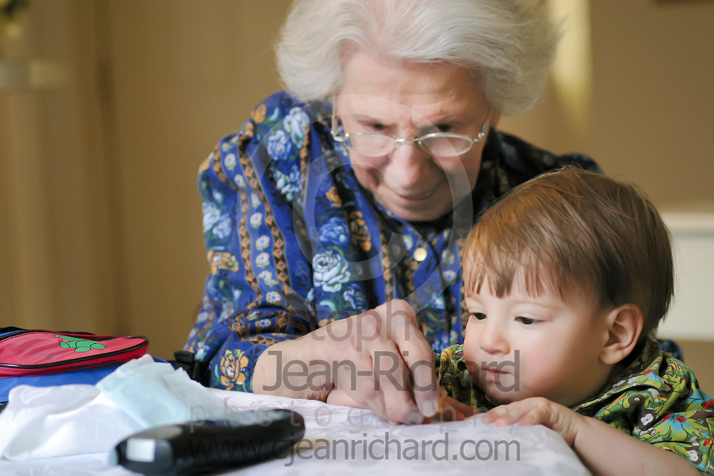 One year old boy attentively watching his great grandmothers hands.