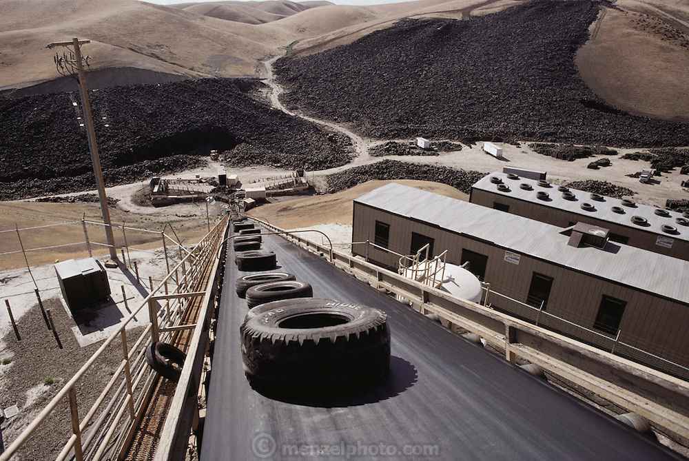 Used tires entering a prototype burning-burning power station in Westley, California. The tires are used as fuel to run an electricity generator. It is estimated that one tire can serve the energy needs of the average northern California household for a day. A tire mountain containing around 40 million tires dominates the landscape (background); the plant is expected to burn some 4 million tires annually. Several environmental protection systems reduce emissions from the plant; a smog-control system neutralizes nitrous oxides, a scrubber system removes sulphur & a giant vacuum cleaner removes fly ash. Both the sulphur & the zinc- containing fly ash are recycled. (1988).
