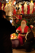 A mechanical Santa on 84th Street is visited and photographed by people of all ages.