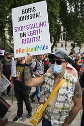 A LGBTI+ protester holds a placard in Parliament Square before the first-ever Reclaim Pride march on 24th July 2021 in London, United Kingdom. Reclaim Pride replaced the traditional Pride in London march, which many feel has become too commercial and strayed from its roots in protest, and was billed as a People's Pride march for LGBTI+ liberation. Campaigners called for the banning of LGBTI+ conversion therapy, the reform of the Gender Recognition Act, the provision of a safe haven for LGBTI+ refugees and for LGBTI+ people to be decriminalised worldwide and marched in solidarity with Black Lives Matter.