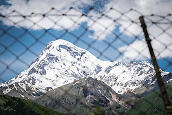 14 June 2016, Kazbegi (Stepantsminda), Georgia: The dormant stratovolcano of Mount Kazbek and the Gergeti Glacier, seen through metal fence in the village of Kazbegi.