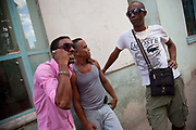 Young Afro Cuban men in the street talking and playing on their mobile phones, Habana Vieja old Havana.