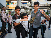 22 MAY 2015 - BANGKOK, THAILAND: Thai police scuffle with and arrest anti-coup protestors in front of the Bangkok Art and Culture Centre. The Thai military seized power in a coup on May 22, 2014. There were small protests throughout Bangkok Friday to mark the first anniversary of the coup. Police arrested protestors at several locations. The most serious protest was at Bangkok Art and Culture Centre (BACC) where about 100 protestors, mostly students, faced off against police for several hours. Police made numerous arrests at the BACC protest.     PHOTO BY JACK KURTZ
