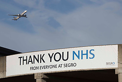 """© Licensed to London News Pictures.13/02/2021, London, UK. An airplane flies over the NHS sign near the drive-through testing centre in Heathrow Airport in West London. Arriving passengers from 22 """"red list"""" countries need to quarantine in the hotel rooms to prevent a new spread of coronavirus. Photo credit: Marcin Nowak/LNP"""