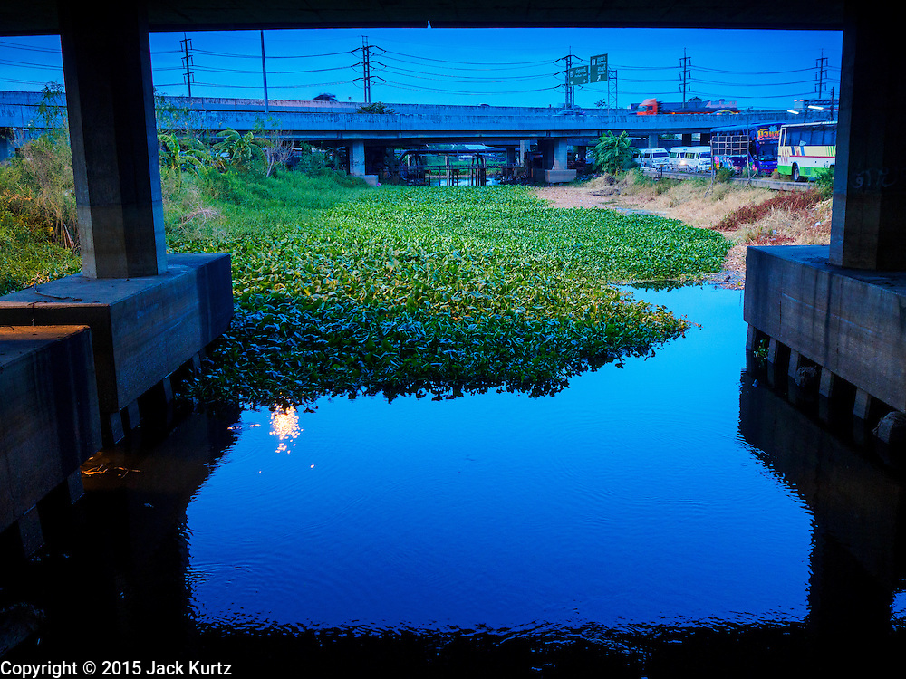 14 JULY 2015 - THAILAND:  A nearly empty khlong (irrigation canal) near Bangkok. The drought that has crippled agriculture in central Thailand is now impacting residential areas near Bangkok. The Thai government is reporting that more than 250,000 homes in the provinces surrounding Bangkok have had their domestic water cut because the canals that supply water to local treatment plants were too low to feed the plants. Local government agencies and the Thai army are trucking water to impacted communities and homes. Roads in the area have started collapsing because of subsidence caused by the retreating waters. Central Thailand is contending with drought. By one estimate, about 80 percent of Thailand's agricultural land is in drought like conditions and farmers have been told to stop planting new acreage of rice, the area's principal cash crop.      PHOTO BY JACK KURTZ