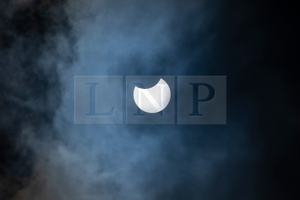 © Licensed to London News Pictures. 10/06/2021. LONDON, UK.  A partial eclipse of the Sun is seen over north west London through low clouds.  The Moon is passing in front of the Sun, blotting out up to 38% of its disc.  First contact is at 10.08am, maximum eclipse at 11.13am and ends at 12.22pm (BST).  Photo credit: Stephen Chung/LNP