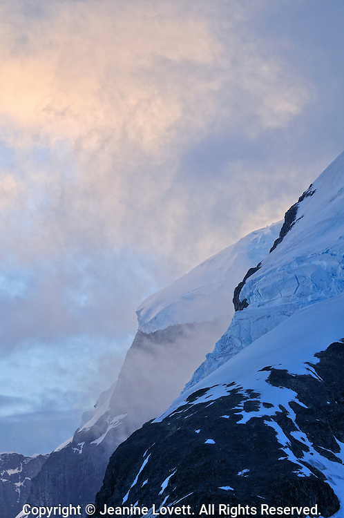 mysterious Misty low clouds hang over Antarctic Peninsula, Errera Channel black cliffs.