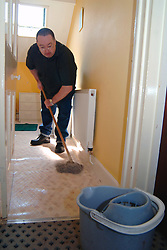Resident at a homeless hostel cleans the bathroom; Liverpool, The hostel is funded through the Supporting People government scheme to help vulnerable people improve their lives,  The hostel helps men overcome drink; drug and mental health problems,