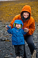 Portrait of mom and son on a rainy beach that is blanketed in kelp in Seward, Alaska.
