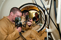 Navy recruits practice deep water diving using a surface supply line umbiical cord for deep water dives. The equipment is precise and the maneuvers must be perfected to ensure safe recovery.