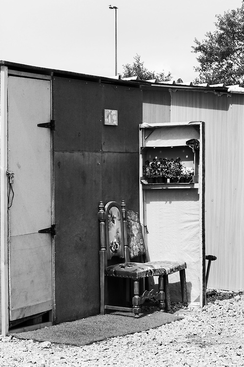 In an attempt to make it feel like home, each hut was decorated with whatever objects the refugees could find. Here, a few flowers were planted and watered daily.  Dunkirk Migrant Camp, France<br /> May 2016