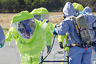 New Hampton, New York - A member of the Orange County Hazardous Materials (HAZMAT) Response Team, goes through a decontamination wash during a drill that practiced responding to a tanker railcar leak at the Orange County Fire Training Center on Aug. 9, 2014. The Huguenot Fire Department provided the decontamination team.