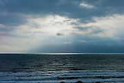 Sun's rays over rough sea at dawn on a windy day at Rosslare, South East Ireland
