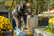 Family members light candles and put them on a grave at the Rakowicki cemetery in Krakow, Poland 2019.