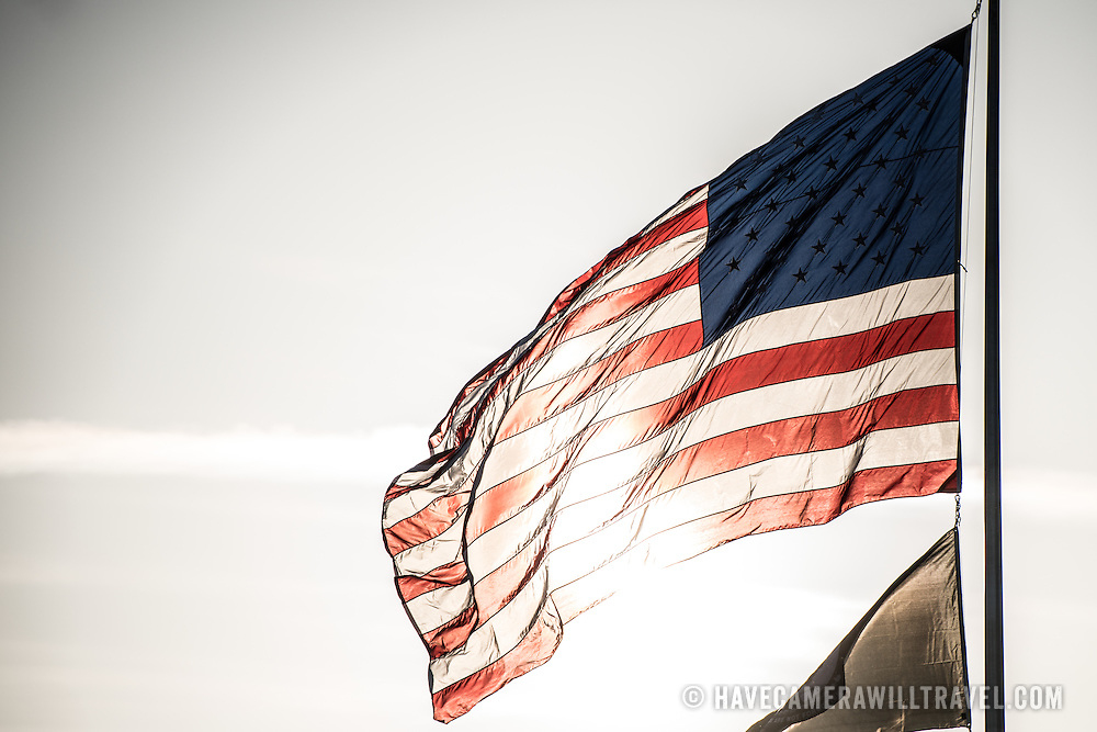An American flag flies in the breeze and is backlit by the direct sun.