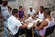 Cuban men of varying ages play  dominoes on a table in the street, Havana Centro, central Havana.