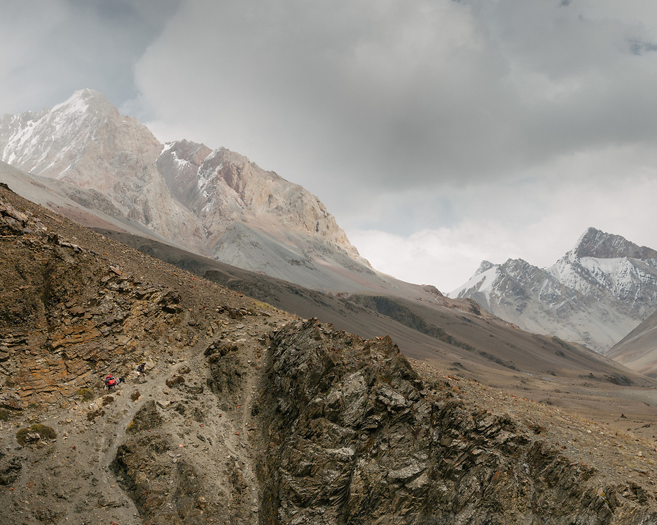 """View towards Sekr Yanj (""""Red Canyon""""), our camp for the night. The tiny red bag on the left, that's mine –this is the point, of no return for us, at the end of this valley, to the right, is the pass leading into Pakistan. Trekking up the Tash Köpruk valley, leading to the Irshad Pass (4950m) into Pakistan. Guiding and photographing Paul Salopek while trekking with 2 donkeys across the """"Roof of the World"""", through the Afghan Pamir and Hindukush mountains, into Pakistan and the Karakoram mountains of the Greater Western Himalaya."""