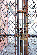 padlocked gate in metal fence