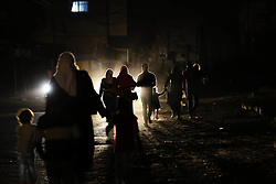 April 14, 2017 - Gaza, Gaza strip, Palestine - Palestinians walk on a road during a power cut in Gaza Strip , The Electricity Authority in Gaza has cut all lines and sources of electricity from the sector since 7 pm on Friday temporarily, adding that this comes in response to popular protest against the ''unjust measures'' practiced in the Gaza Strip, especially the problem of electricity n Gaza City April 14, 2017  (Credit Image: © Momen Faiz/NurPhoto via ZUMA Press)