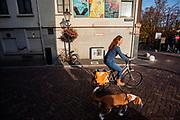 Een vrouw fietst met haar hond aan de lijn door Utrecht.<br /> <br /> A woman cycles with a dog on a leash in Utrecht.