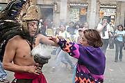 MEXICO CITY, MEXICO: An Aztec holy person conducts a limpia (or cleansing) ceremony, next to the Cathedral, on the Zocalo in Mexico City. Although predominantly Roman Catholic, many in Mexico blend some elements of traditional beliefs into their Catholicism.  02 AUGUST 2003 PHOTO BY JACK KURTZ