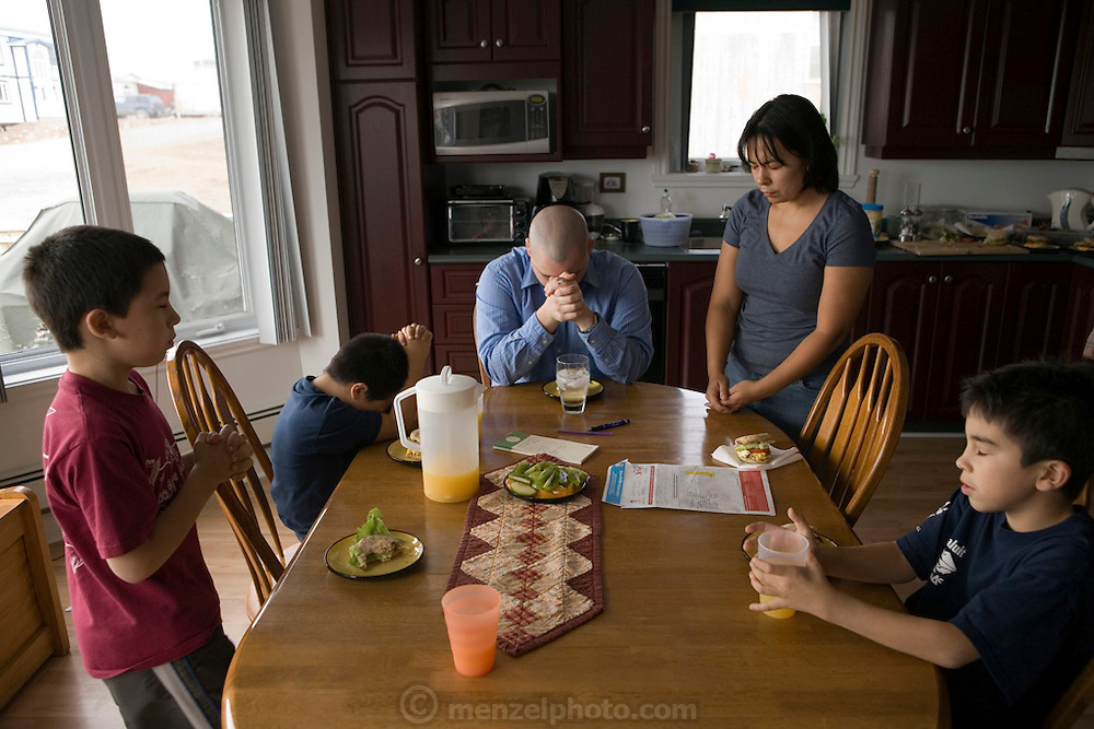 "The Melanson family prays before lunch in Iqualuit, Canada. Iqaluit, with a population of 6,000, is the largest community in Nunavut as well as the capital city. It is located in the southeast part of Baffin Island. Formerly known as Frobisher Bay, the town is at the mouth of the bay of that name, overlooking Koojesse Inlet. ""Iqaluit"" means 'place of many fish'. Canada. The image is part of a collection of images and documentation for Hungry Planet 2, a continuation of work done after publication of the book project Hungry Planet: What the World Eats, by Peter Menzel & Faith D'Aluisio."