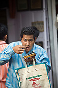 A man eats street food at the Ashok Chat Corner in Chawri Bazaar, Old Delhi India