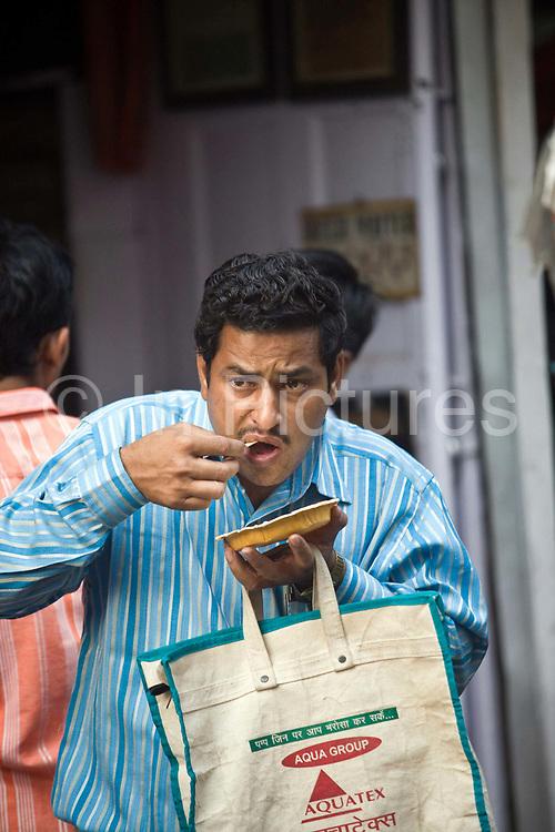 A man eats street food at the Ashok Chat Corner in Chawri Bazaar, Old Delhi India