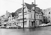 """Y-530316B-01Ladd Carriage House-exterior. SW Broadway & Columbia. Former carriage house of banker William S. Ladd. Built in 1883, rebuilt into specialty shops and stores in 1926 by L.H. Hoffman Company. In addition to use by Hoffman and other businesses in 1953, it was also utilized for apartments. """"Barn exterior with gingerbread is unchanged; original tin roof and still shelters old coachman's quarters in attic."""" From: Sunday Oregonian April 5, 1953 Section 1 Page 26. photo taken March 16, 1953"""