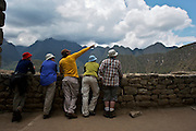 A guide is pointing somewhere to the right side in the ruins of machu picchu