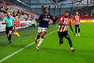 Middlesbrough defender Djed Spence (29) battles with Brentford defender Rico Henry (3), watched by assistant referee Michael George George during the EFL Sky Bet Championship match between Brentford and Middlesbrough at Brentford Community Stadium, Brentford, England on 7 November 2020.