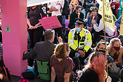 A Metropolitan Police officer asks environmental activists from Extinction Rebellion to move out from under a giant table used to block roads in the Covent Garden area during the first day of Impossible Rebellion protests on 23rd August 2021 in London, United Kingdom. Extinction Rebellion are calling on the UK government to cease all new fossil fuel investment with immediate effect.