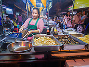 25 OCTOBER 2014 - BANGKOK, THAILAND: A vendor stir fries a customer's dinner at a street food stall near Yaowarat Road in Bangkok. Yaowarat Road is the center of the Bangkok Chinatown neighborhood and is famous for the street food. Most of the food stalls open after sunset.     PHOTO BY JACK KURTZ