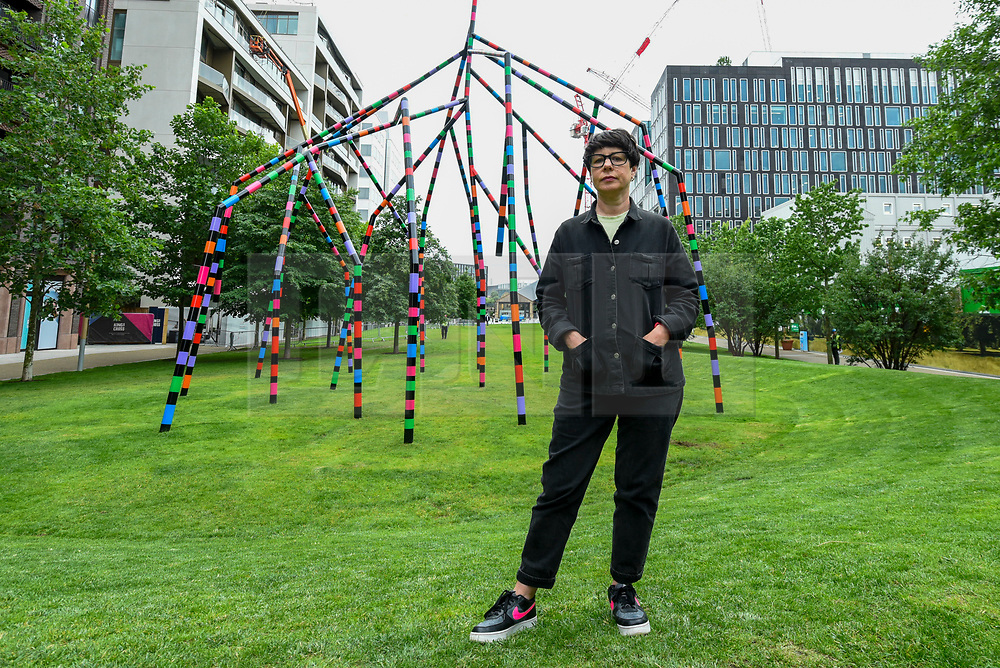 """© Licensed to London News Pictures. 16/07/2020. LONDON, UK.  London-based, Irish artist Eva Rothschild poses at the unveiling next to her work """"My World and Your World"""".  The new 16m high public sculpture in Lewis Cubitt Park in King's Cross resembles a lightning bolt, painted in black, purple, pink, orange, green and red stripes.  The coronavirus lockdown caused the April 2020 launch to be postponed, but the unveiling has been able to go ahead now that certain lockdown restrictions have been eased by the UK government.  Photo credit: Stephen Chung/LNP"""