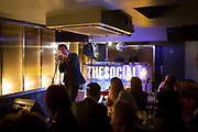 Audience listening carefully to a poet delivering his spoken words at a poetry reading at The Social, a small music and arts venue in central London, UK.