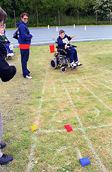 Adult with young wheelchair user taking part in Mini games sports event held at Stoke Mandeville Stadium,