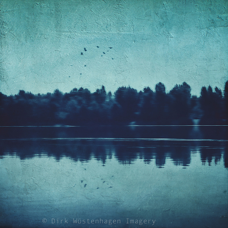Abstract landscape in blue tones - trees reflecting on a river surface