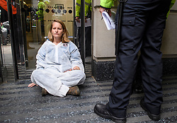 © Licensed to London News Pictures. 08/10/2019. London, UK. An Extinction Rebellion activist glued to the Department for Transport in Westminster. Activists have converged on Westminster for a second day, blockading roads in the area and calling on government departments to 'Tell the Truth' about what they are doing to tackle the Emergency. Photo credit: Ben Cawthra/LNP