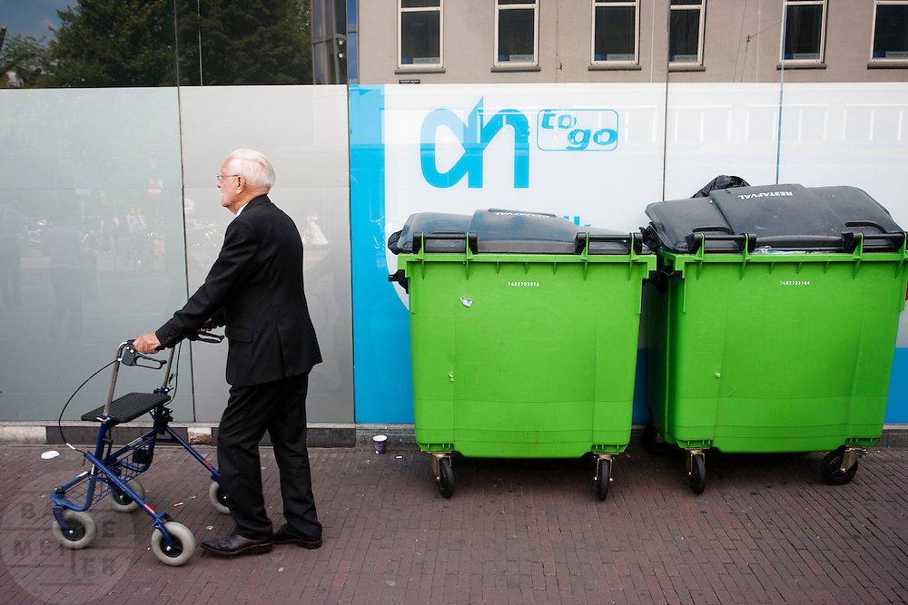 Een man met rollator loopt langs de Albert Heijn To Go.<br /> <br /> An older man is walking past garbage bins.