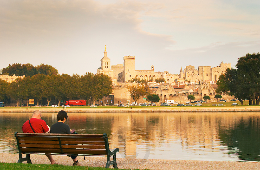 The Pope's palace in Avignon from across the river reflected in the water. A couple sitting on a bench. Avignon, Vaucluse, Provence, Alpes Cote d Azur, France, Europe