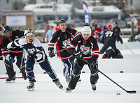 """Barry Enos from the Looney Bin takes control of the puck against The Dirty Lew's in the """"Just for Fun"""" division during first round action on Meredith Bay for the New England Pond Hockey Classic Friday morning.  (Karen Bobotas/for the Laconia Daily Sun)"""