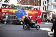 A motorcyclist drives with a EU flag on the Marble Arch road in London city during the People's Vote March