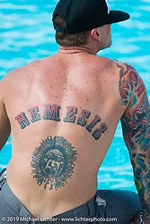 Marchin Lewandowski shows off his back tattoo around the pool at the Broken Spoke County Line during the annual Sturgis Black Hills Motorcycle Rally. SD, USA. August 7, 2014.  Photography ©2014 Michael Lichter.