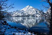Snowy Teton peaks reflect in Jenny Lake, Grand Teton National Park, Wyoming, USA.