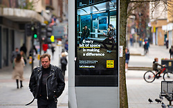 Glasgow, Scotland, UK. 23 March 2021. On the first anniversary of the coronavirus pandemic lockdown the streets in Glasgow city centre are still quiet with only essential shops open. Pic; government health warning and advice still being displayed on video screens on the street. Iain Masterton/Alamy Live News